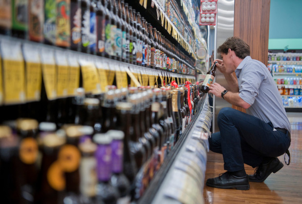Evan Nelson, a sales representative for Wine Warehouse, stocks shelves and aligns beer bottles in a display at the newly opened and sprawling wine, spirits and beer section of the Pavilions grocery store in Rancho Santa Margarita on Monday, February 13, 2017.  Photo By Jeff Antenore, Contributing Photographer